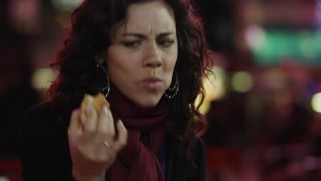 slo mo cu td young woman having hot dog in times square at night / new york city, new york state, usa - ホットドッグ点の映像素材/bロール