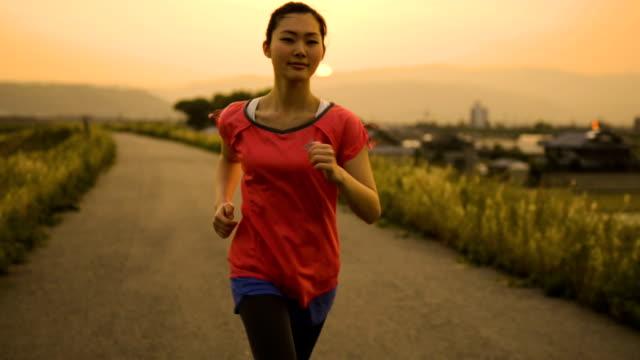 川の土手で夕日にジョギングを持つ若い女性 - ジョギング点の映像素材/bロール