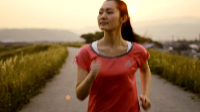Young woman having jogging at sunset at river bank