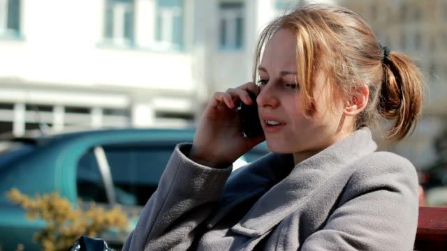 vídeos de stock, filmes e b-roll de jovem mulher tendo não conversas agradáveis no telefone ao ar livre - batendo com a cabeça na parede
