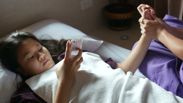 young woman having relaxing  with Thai massage and using phone