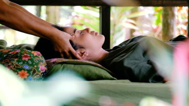 Junge Frau, die mit Thai-Massage im Garten entspannen