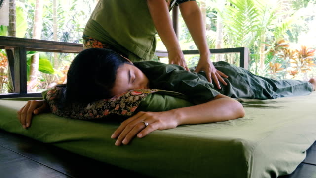 Young woman having relaxing with Thai massage at garden
