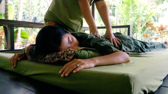 Jonge vrouw met ontspannen met Thaise massage in de tuin