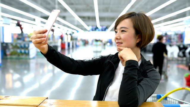 young woman having selfie at the market - fotohandy stock-videos und b-roll-filmmaterial