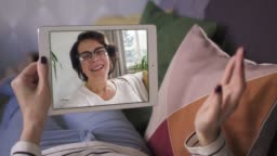 Young woman having video call via tablet talking to mom
