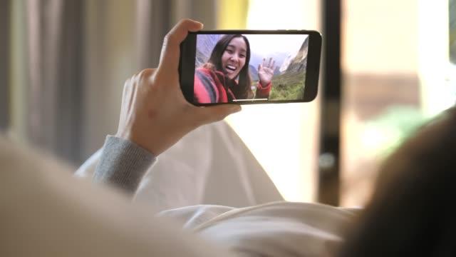 vídeos de stock, filmes e b-roll de mulher nova que tem o bate-papo video que prende a câmara web esperta do telefone que conversa ao amigo que encontra na cama - câmera de conferência