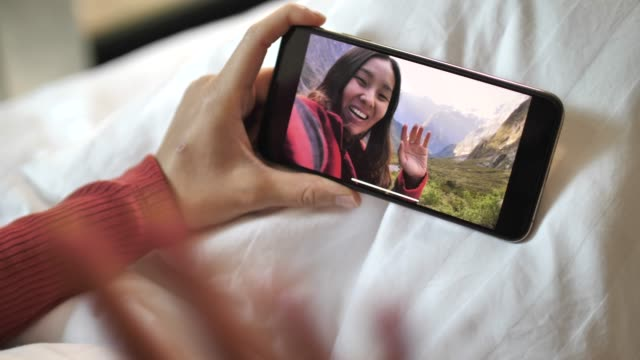 young woman having video chat on smart phone webcam chatting to friend lying in bed at home - voip stock videos & royalty-free footage