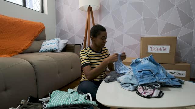 vídeos y material grabado en eventos de stock de mujer joven que ayuda a separar la ropa para la donación a la organización de ayuda - sólo mujeres jóvenes