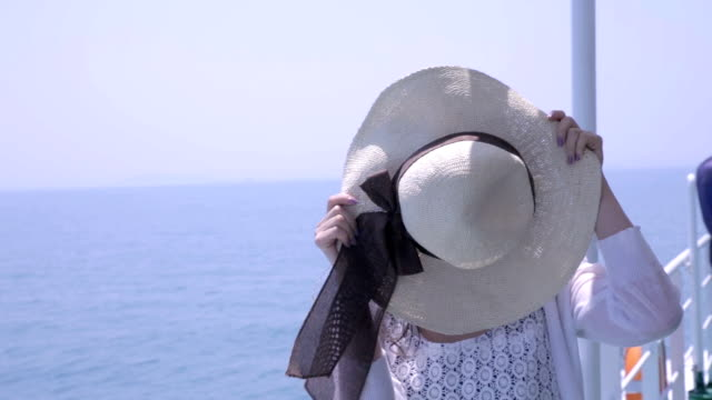 young woman hiding her face with straw hat then revealing with smiling face - hiding stock videos and b-roll footage