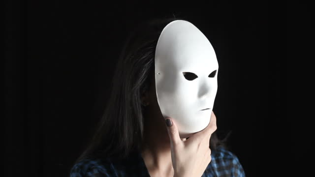 young woman hiding true color behind mask - obscured face stock videos & royalty-free footage