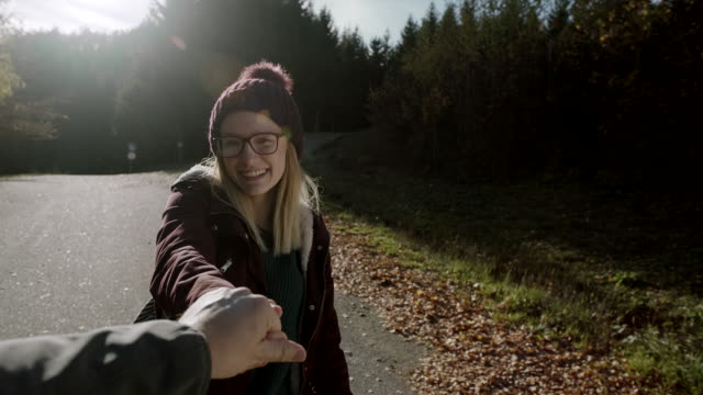 Young woman hiker holding her boyfriend by the hand