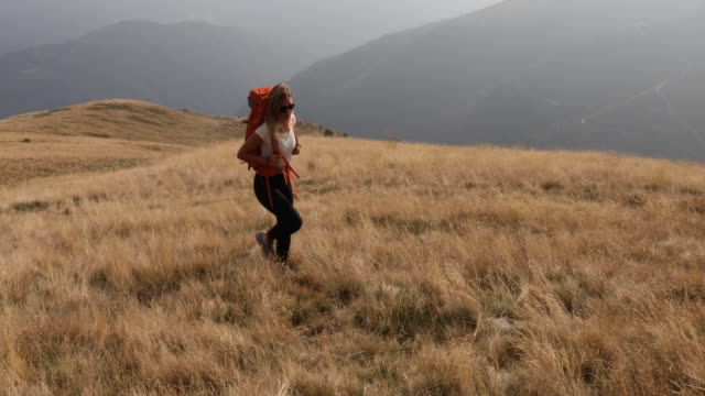young woman hikes through grassy alpine meadow - viewpoint stock videos & royalty-free footage