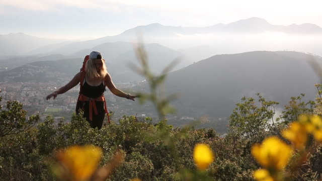 young woman hikes through hills past flowering shrubs - liguria stock videos & royalty-free footage