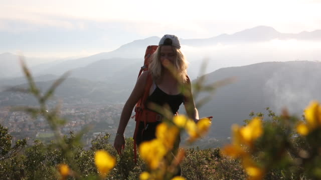 Young woman hikes through hills past flowering shrubs