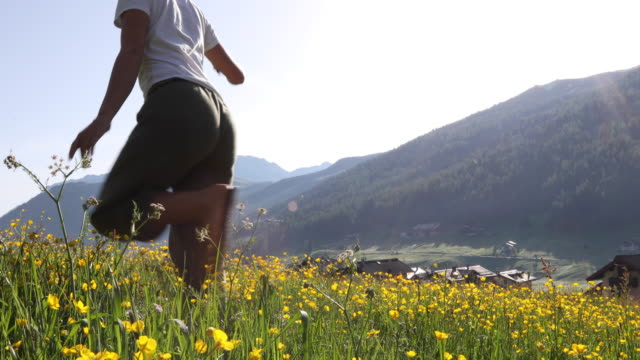 young woman hikes through wildflower meadow at sunrise - t shirt stock videos & royalty-free footage