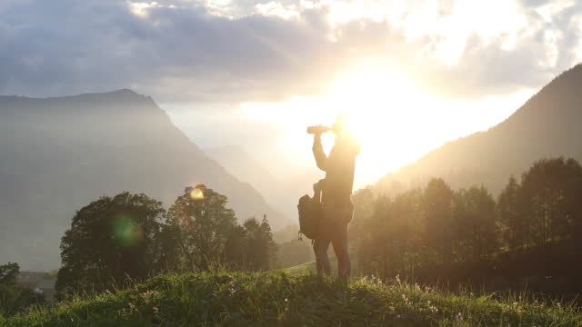 young woman hikes to mountain hillcrest - day stock-videos und b-roll-filmmaterial