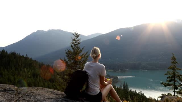 Junge Frau Wanderungen an die Spitze der Felsvorsprung bei Sonnenaufgang