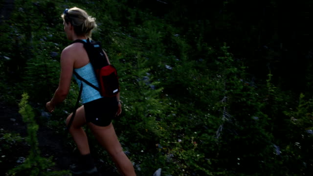 Young woman hikes up through mountain meadow