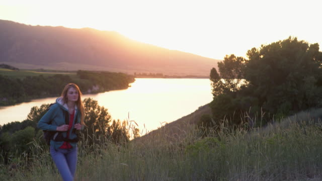 WS young woman hiking by a lake at sunset