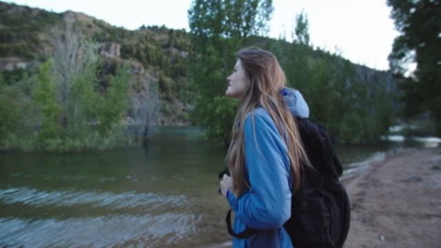 young woman hiking by a lake in the mountains - endast unga kvinnor bildbanksvideor och videomaterial från bakom kulisserna