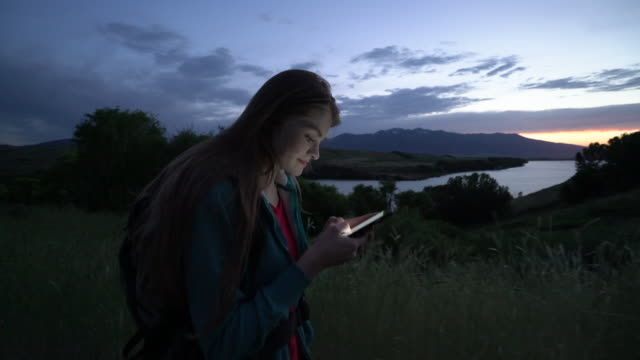 vídeos de stock e filmes b-roll de sm ms young woman hiking by a lake using her phone at dusk - teenage girls