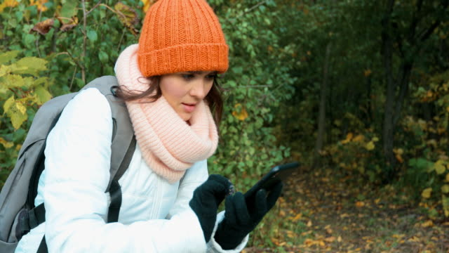 young woman hiking in forest in autumn and using mobile phone - woolly hat stock videos and b-roll footage