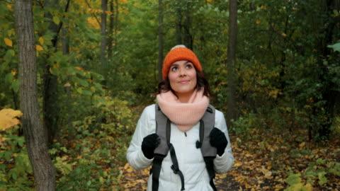 stockvideo's en b-roll-footage met jonge vrouw wandelen in bos in de herfst - autumn