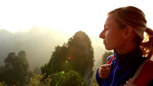 Young woman hiking in nature contemplating spectacular view