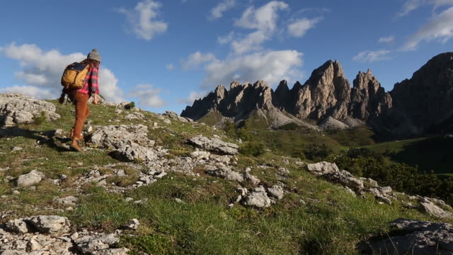 A young woman hiking in the Dolomite Mountains of Italy.
