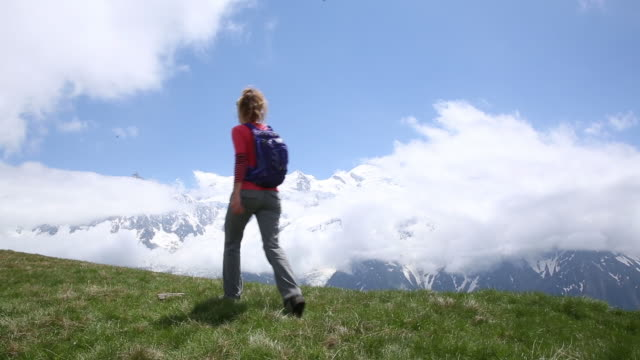 stockvideo's en b-roll-footage met a young woman hiking in the mountains of chamonix france. - one mid adult woman only