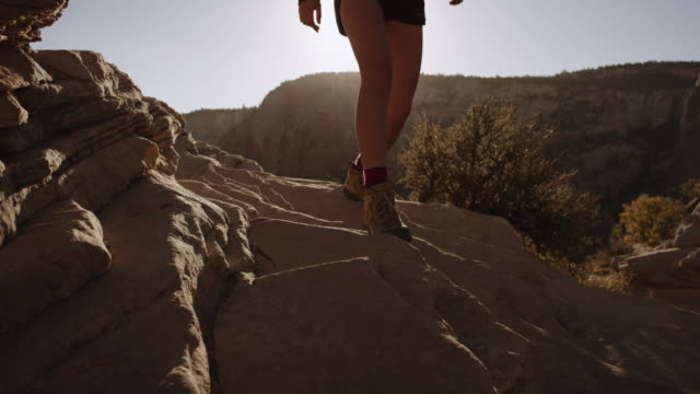 4k uhd: young woman hiking near cliff edge - canyon stock videos & royalty-free footage