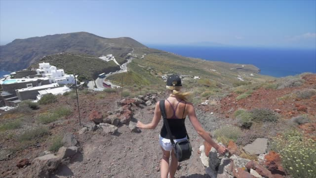vidéos et rushes de a young woman hiking on a trail, traveling in santorini, greece, europe. - slow motion - grèce