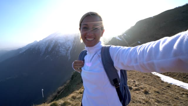 Young woman hiking reaches mountain top and takes selfie portrait