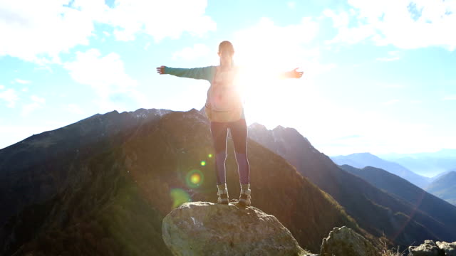 Young woman hiking reaches mountain top, outstretches arms