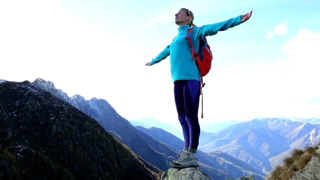 Junge Frau Wandern erreicht den Gipfel des Berges feiert