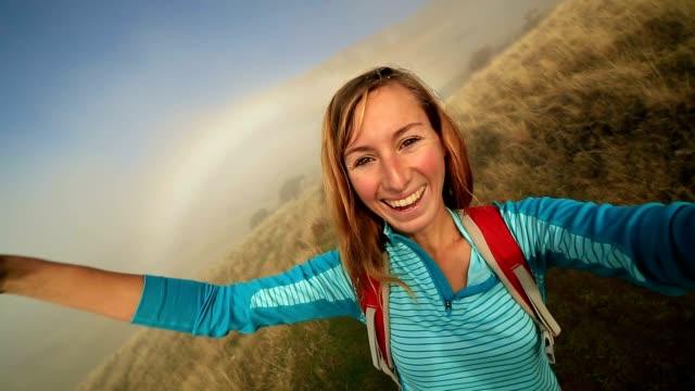 Junge Frau Wandern nimmt Selfie im Nebel, Regenbogen