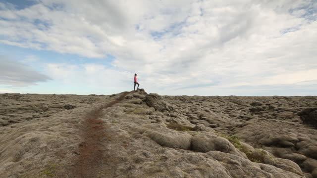 a young woman hiking through a mossy field in iceland. - solo una donna di età media video stock e b–roll