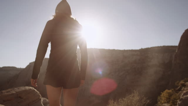 4k uhd: young woman hiking to cliff edge - canyon stock videos and b-roll footage