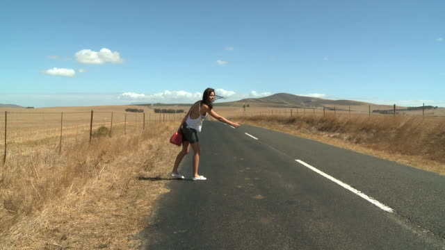 WS Young woman hitchhiking on road / Cape Town, South Africa