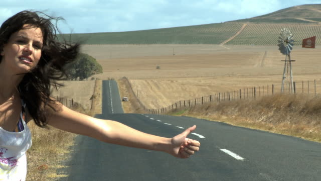 ws young woman hitchhiking on road / cape town, south africa - ヒッチハイキング点の映像素材/bロール