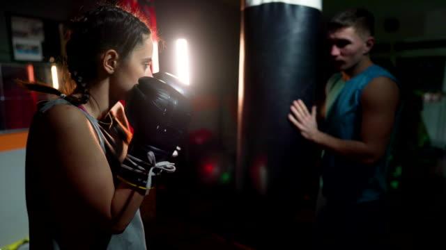 ボクシングバッグを打つ若い女性 - 女子ボクシング点の映像素材/bロール