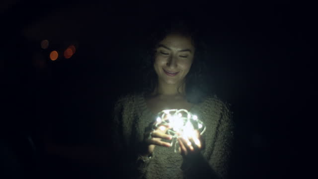 young woman holding a ball of light at night - 電気部品点の映像素材/bロール
