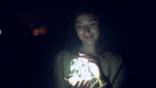 MS Young woman holding a ball of light at night