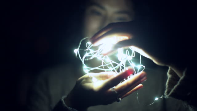 cu young woman holding a ball of light at night - bizarre stock videos & royalty-free footage