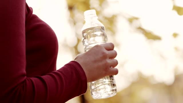 持つ若い女性のボトルウォーター - ウォーターボトル点の映像素材/bロール
