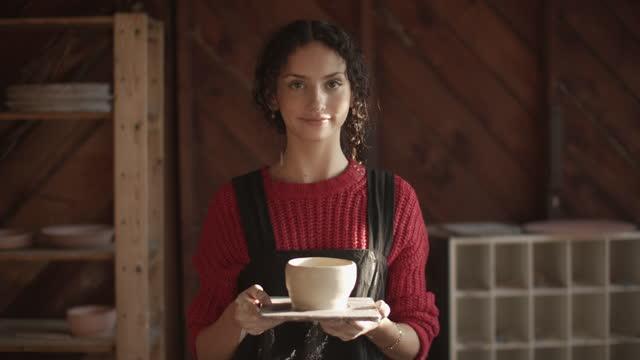 vidéos et rushes de cu young woman holding a bowl she made out of clay - entrepreneur