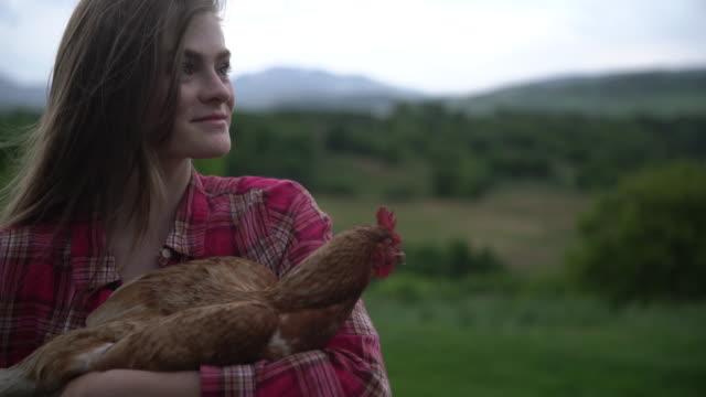 stockvideo's en b-roll-footage met cu young woman holding a chicken in her arms - alleen één tienermeisje