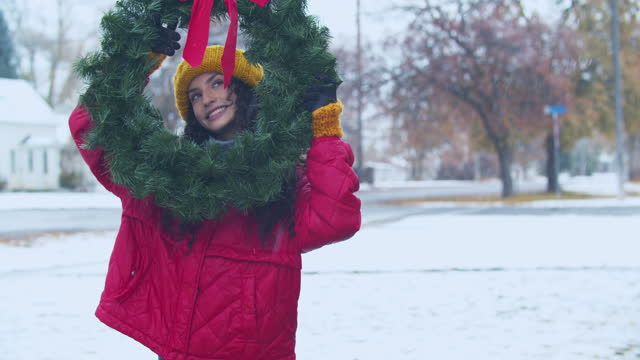 young woman holding a christmas wreath in the snow - wreath stock videos & royalty-free footage