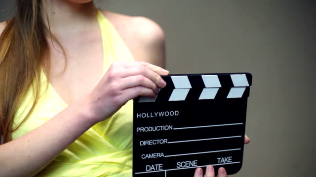 young woman holding a clapper - film director stock videos & royalty-free footage